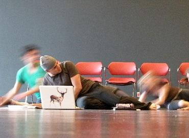 Man laying on the ground with laptop in front of red chairs and blurry dancers