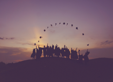 silhouette of graduating students standing on a hill throwing their caps in the air